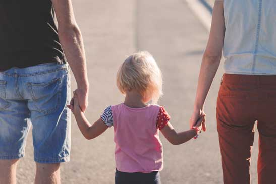 couple holding hands with a small child